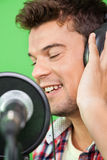 Smiling Singer Performing In Recording Studio. Closeup of smiling male singer performing in recording studio Stock Photos