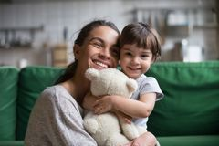 Smiling single young mum embracing little daughter. Smiling single young mum embracing little preschool daughter with toy, playing in living room at home, mother royalty free stock images
