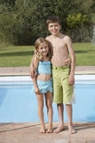 Smiling Sister And Brother Standing Against Pool. Full length portrait of a smiling sister and brother standing against the pool Stock Photo