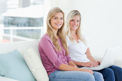 Smiling sisters hold a laptop as they look sideways into the cam Stock Image