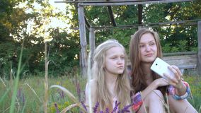 Smiling sisters making selfie sitting on a lawn stock footage