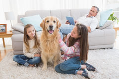 Smiling sisters petting their golden retriever on rug Stock Image