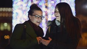 Smiling Sisters Using Mobile Phone on a Night Street with Christmas Lights Decorations. Two Brunette Girls Laughing. Looking at Gadget Screen. Blurred Xmas stock video footage