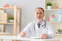 Smiling sitting at table. Ready to start. Smiling mature doctor sitting at table with documentation while being busy at work royalty free stock photo