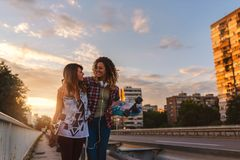 Smiling skate girls holding long-boards walking outdoors in the street Stock Image