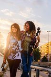 Smiling skate girls holding long-boards walking outdoors in the street Stock Photos