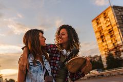 Smiling skate girls holding long-boards walking outdoors in the street Stock Photography