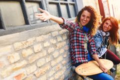 Smiling skateboarding girls sitting in the street hanging out Royalty Free Stock Images