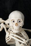 Smiling skeleton. In a contortion act. Black background Stock Photo