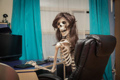 Smiling skeleton in a wig sitting in room on black leather chair behind the desktop Royalty Free Stock Photo
