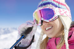 Smiling skier adjusting goggles Royalty Free Stock Image