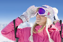 Smiling skier adjusting goggles Royalty Free Stock Photography