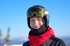 Smiling skier in helmet. Smiling skier wearing a helmet at the blue sky Royalty Free Stock Photo