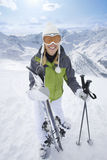 Smiling skier standing with skis and poles on mountain top Royalty Free Stock Photos