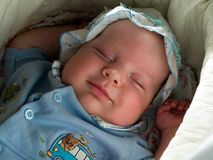 Smiling sleeping baby boy. Smiling face of sleeping boy in the home nursery Stock Photography
