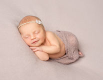 Smiling sleeping newborn girl covered with shawl Royalty Free Stock Photography