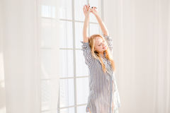 Smiling sleepy woman waking up and stretching near window Stock Images