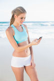 Smiling slender blonde in sportswear texting Stock Photography