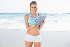 Smiling slender blonde in sportswear using tablet Stock Photos