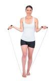 Smiling slender model jumping rope Royalty Free Stock Photo