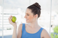 Smiling slender woman in sportswear holding green apple Stock Photos
