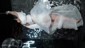Slim dancer girl spins on pylon, enjoy music, perform skill dance in shiny club