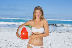 Smiling slim woman holding beach ball Royalty Free Stock Photos