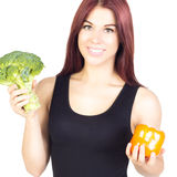 Smiling slim woman holding peppers and broccoli . Diet and prope Royalty Free Stock Photography
