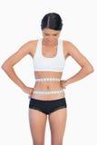 Smiling slim woman measuring her waist Royalty Free Stock Photos