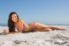 Smiling slim young woman posing while lying Royalty Free Stock Images