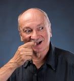 Smiling sly elderly man Royalty Free Stock Photo