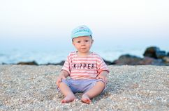 Smiling small boy sitting on the sand near sea in blue hat and striped clothes. Summer concept. Holiday relaxing, beach. Vacation Royalty Free Stock Photo