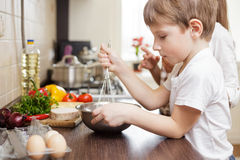 Smiling small boy whisking eggs in bowl on table Stock Images