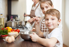 Smiling small boy whisking eggs in bowl on table Stock Image