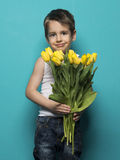 Smiling small boy with yellow tulip . International Womens, Moth Royalty Free Stock Photo
