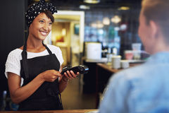 Smiling small business owner taking payment. Smiling attractive African American small business owner taking payment from a customer processing a credit card Royalty Free Stock Images