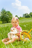 Smiling small girl cuddles rabbit in green meadow Stock Photos