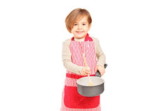 Smiling small girl holding a frying pan and kitchen utensil Stock Images