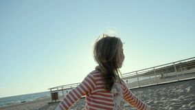Smiling small girl stands, runs, and jumps on a sea beach, at sunset in slo-mo. A funny four year old girl dressed in a striped blouse, and a red dress, stand stock footage