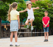 Smiling small kids playing with jumping rope Royalty Free Stock Photo