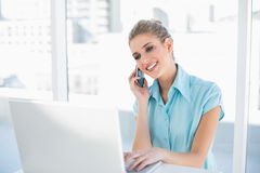 Smiling smart businesswoman on the phone while using laptop Stock Photos