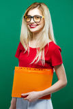 Smiling Smart Female Student in Eyeglasses with Folder of Documents in Hands Standing on Green Background in Studio. Stock Photography