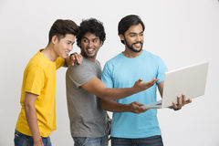 Smiling Smart male friends looking laptop computer Royalty Free Stock Image