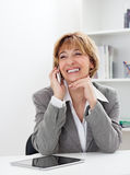 Smiling Smart phone mature businesswoman Royalty Free Stock Image