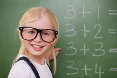 Smiling smart schoolgirl pointing at something Stock Photo