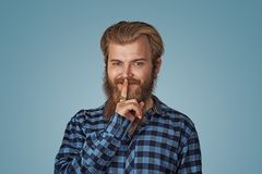Smiling smug man hipster guy keeps a secret royalty free stock photography