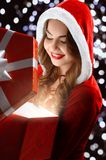 Smiling Snow Maiden in red suit opens a gift for New Year 2018,2019 Stock Images