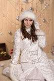 Smiling snow maiden. Maiden sit in white clothes with toys Stock Image