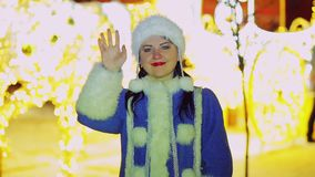 Smiling snow maiden waving her hand in front of the radiant carriage lights