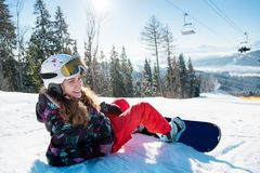 Smiling snowboarder girl lying on snow in sun rays royalty free stock photography
